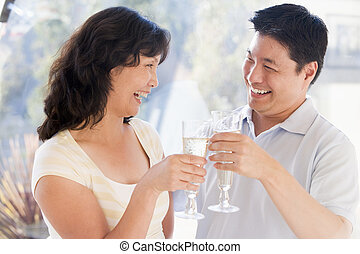 Couple toasting champagne and smiling