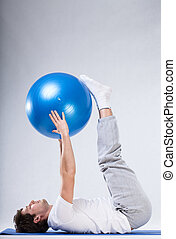 Exercising with big ball - A man doing pilates exercises...
