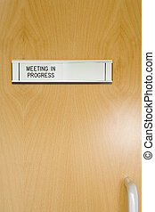 A Closed Office Door, With \'Meeting In Progress\' Sign