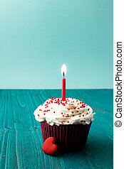 sweet little birthday cake with candles, blue background