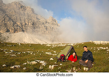 Young people camping while hiking in the mountains