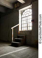 inside an old industrial building, window, wooden stairs