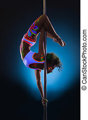 Slender young woman dancing on pole