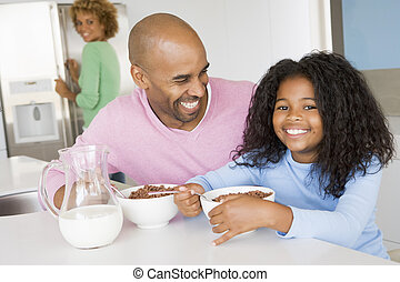 Father Sitting With Daughter As She They Eat Breakfast With...