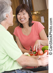 Woman Talking To Husband While Chopping Vegetables