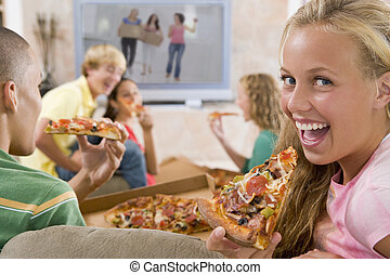 Teenagers Hanging Out In Front Of Television Eating Pizza