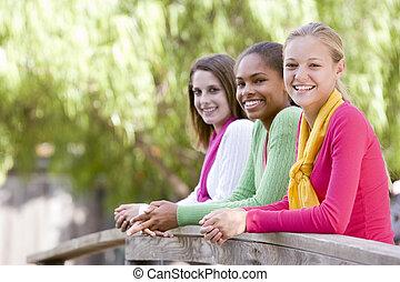 Teenage Girls Leaning On Wooden Railing