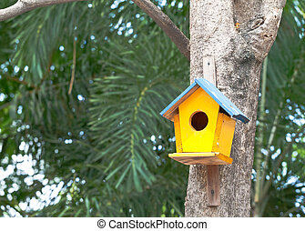 yellow birdhouse on a tree