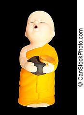 Doll clay baby monk with alms bowl isolated on black...