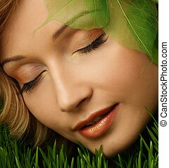 Dreaming young woman lying on a fresh spring grass