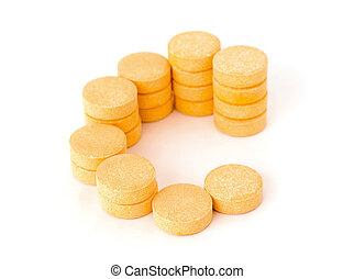 C vitamin pills over white