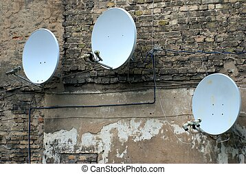 Satellite dish antenna on the old house wall - Satellite...