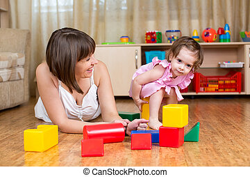 mother and kid play toys at home