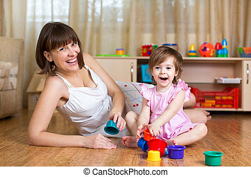 kid girl and mom playing together with cup toys
