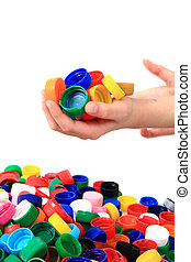 color plastic caps in human hands isolated on the white...