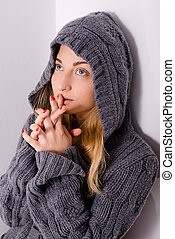beautiful young blond woman girl in hood praying and looking...