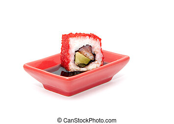 Sushi roll dipped in soy sauce, isolated over white