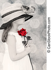 Little girl holding a red rose - young child wearing an...