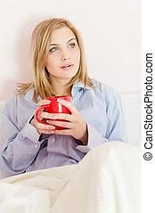 Beautiful happy smiling young woman in bed holding cup of...