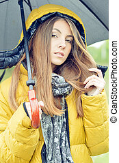 Young pretty woman with umbrella wearing warm yellow coat