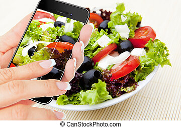 hand making photo of salad by cellphone