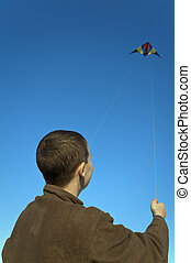 Boy flying a kite back close - Boy flying a kite with clear...