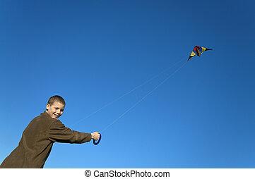 Boy flying a kite far slant - Boy flying a kite with clear...