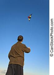 Boy flying a kite back far - Boy flying a kite with clear...