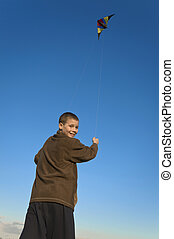 Boy flying a kite face far - Boy flying a kite with clear...