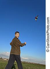 Boy flying a kite face far slant - Boy flying a kite with...