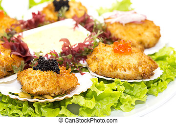 fried scallops decorated with caviar and greens