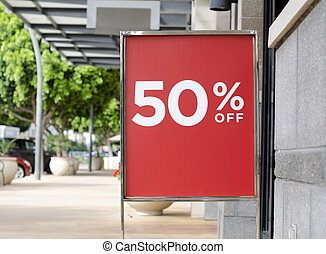 Sale sign outside retail store - 50% off red sale sign...