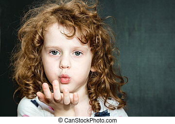 Curly girl blowing mouth with hand