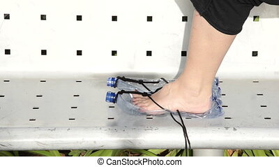 She wears a plastic bottle sandals - Woman wears a plastic...