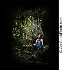 meditating - Yong cross-legged woman relaxing on the jungle...