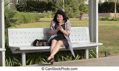 Woman cries calling by the phone sitting on a park bench
