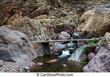 Trekker crossing bridge - A trekker crossing a bridge on the...