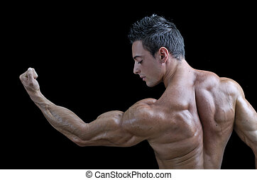 Muscular young bodybuilder's back. Looking at bicep -...