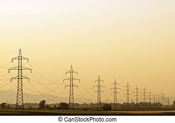 Transmission line at sunset with clear orange sky and no end...