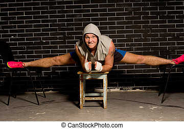 Fit supple young boxer working out balancing on three stools...
