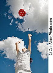 Girl playing with a red ball