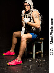 Boxer sitting on a stool waiting for his fight