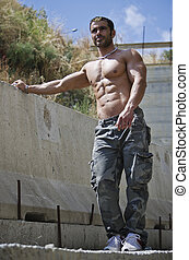 Muscle man shirtless outdoors leaning against concrete wal -...