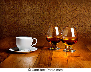 Two goblets of brandy and cup of hot coffeeon wooden old...