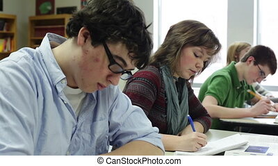 students taking notes - High school students taking notes in...