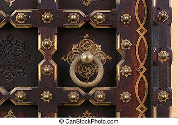 ancient doorhandle - old metal door handle on a wooden door
