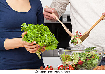 Kitchen couple - Couple preparing salad in the kitchen at...