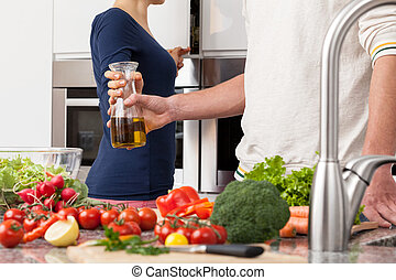 Healthy cooking - Wife gives husband olive oil to prepare...