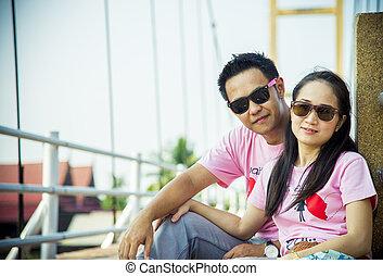 Lovely couple sit on the bridge1