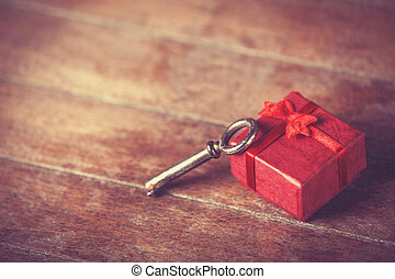 Retro key and little red gift on wooden table.